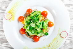 Fresh salad with chicken breast, baby spinach, lettuce, cherry tomatoes and cheese on wooden background Stock Images