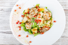 Fresh salad with chicken breast, melon, pineapples, pomegranate seeds, lettuce leaves and almond on plate on wooden background Royalty Free Stock Photo
