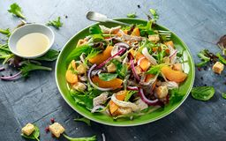 Fresh salad with chicken breast, peach, red onion, croutons and vegetables in a green plate. healthy food Royalty Free Stock Images