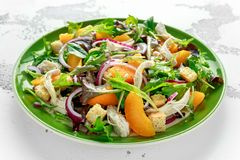 Fresh salad with chicken breast, peach, red onion, croutons and vegetables in a green plate. healthy food Royalty Free Stock Photography