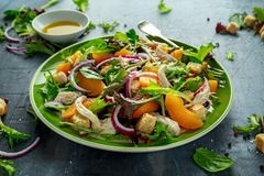 Fresh salad with chicken breast, peach, red onion, croutons and vegetables in a green plate. healthy food Stock Photos