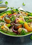 Fresh salad with chicken breast, peach, red onion, croutons and vegetables in a green plate. healthy food Stock Images