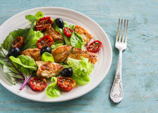 Fresh salad with chicken breast, sun-dried tomatoes, green salad and olives on a white plate Stock Photos