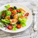 Fresh salad with chicken breast, sun-dried tomatoes, green salad and olives on a white plate Stock Image