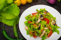 Fresh salad with chicken, mushrooms, lettuce, tomato and mustard dip. Dark stone background. Top view. Close-up Stock Image