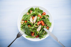 Fresh salad with chicken, tomato and greens spinach, arugula on blue wooden background top view Stock Photography