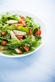 Fresh salad with chicken, tomato and greens (spinach, arugula) on blue wooden background close up Royalty Free Stock Photography