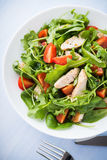 Fresh salad with chicken, tomato and greens (spinach, arugula) on blue wooden background top view Stock Photos