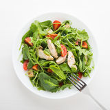 Fresh salad with chicken, tomato and greens (spinach, arugula) top view Stock Photography