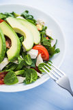 Fresh salad with chicken, tomatoes, spinach and avocado on blue wooden background close up Royalty Free Stock Photos