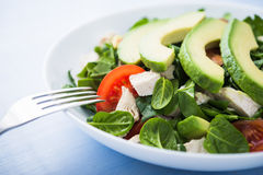 Fresh salad with chicken, tomatoes, spinach and avocado on blue wooden background close up Royalty Free Stock Images