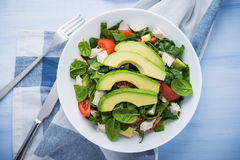 Fresh salad with chicken, tomatoes, spinach and avocado on blue wooden background top view Stock Image