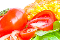 Fresh salad close-up. Corn, carrot, red tomato, green lettuce leaves Royalty Free Stock Photos