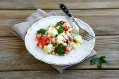 Fresh salad with couscous and vegetables on a white plate Stock Images