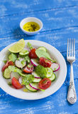 Fresh salad with cucumber, radish, cherry tomatoes and spinach. On a blue wooden background Stock Photography