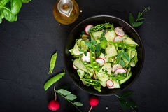 Fresh salad of cucumbers, radishes, green peas and herbs Royalty Free Stock Image