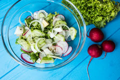 Fresh salad of cucumbers, radishes and herbs on wooden table. Top view. Fresh salad of cucumbers, radishes and herbs. Top view Royalty Free Stock Images