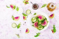 Fresh salad of cucumbers, watermelon radishes and arugula. Royalty Free Stock Images