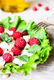 Fresh salad with feta cheese, raspberry, pine nuts and olive oil in a plate, selective focus. Healthy food royalty free stock photo