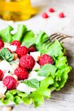 Fresh salad with feta cheese, raspberry, pine nuts and olive oil in a plate, selective focus. Healthy food stock images