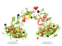 Fresh salad with flying vegetables ingredients Stock Photos