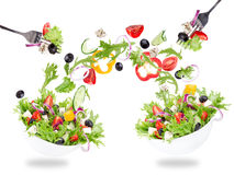 Fresh salad with flying vegetables ingredients Royalty Free Stock Photo
