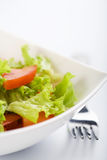 Fresh salad and fork. Fresh salad in white bowl and fork Stock Photo