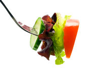 Fresh salad on fork. Isolated on white background Royalty Free Stock Images