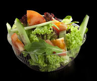 Fresh salad of fresh vegetables. On a black background royalty free stock photos