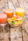 Fresh salad with fruits in glass bowl on wooden table. Royalty Free Stock Images