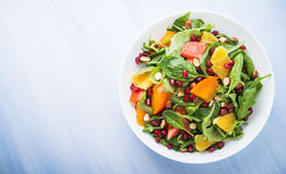 Fresh salad with fruits and greens on blue wooden background top view Stock Photography