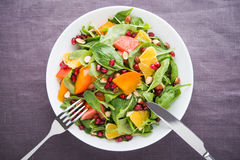 Fresh salad with fruits and greens on dark canvas background top view Stock Images