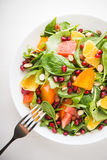 Fresh salad with fruits and greens on white background top view Stock Images