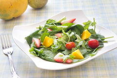 Fresh salad with fruits vegetables and greens. Homemade salad with spring greens spinach, fruits and vegetables. Arranged in a white bowl on a table covered with Royalty Free Stock Photo