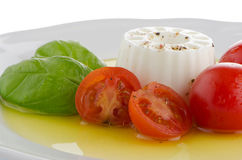 Fresh salad. With goat cheese, tomato and basil pesto on a white plate Stock Photos