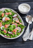 Fresh salad with green peas, spinach, radish and smoked salmon on a ceramic plate Stock Photos