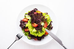 Fresh salad with green and purple lettuce, tomatoes and cucumbers on white wooden background top view Stock Photos