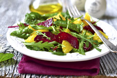 Fresh salad from greens,beetroot and orange. Fresh salad from greens,beetroot and orange on rustic background Stock Photo
