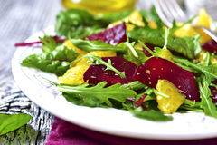 Fresh salad from greens,beetroot and orange. Fresh salad from greens,beetroot and orange on rustic background Royalty Free Stock Image