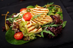 Fresh salad with grilled cheese, tomatoes, capers, lettuce. And arugula royalty free stock photography