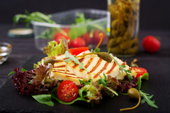 Fresh salad with grilled cheese, tomatoes, capers, lettuce a. Nd arugula Royalty Free Stock Photography