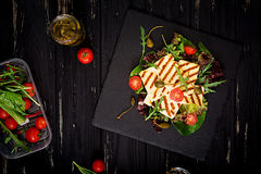 Fresh salad with grilled cheese, tomatoes, capers, lettuce and arugula. Stock Photo