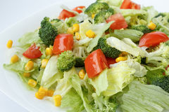 Fresh salad with iceberg lettuce, tomatoes, broccoli and sweet corn on a white plate Stock Images