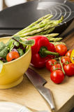 Fresh salad ingredients waiting to be prepared. In a kitchen with tomatoes, red bell pepper, leafy herbs and asparagus on a wooden chopping board with a sharp Royalty Free Stock Photo