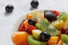 Fresh salad from kiwi, oranges, plums, grapes and chia seeds close up. Healthy lifestyle. Vegetarian food royalty free stock image
