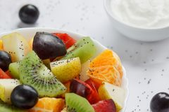 Fresh salad from kiwi, oranges, plums, grapes and chia seeds. Close up. Healthy lifestyle. Vegetarian food stock photography