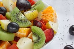 Fresh salad from kiwi, oranges, plums, grapes and chia seeds. Close up. Healthy lifestyle. Vegetarian food stock image