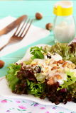 Fresh salad leaves with yogurt and hazelnuts on a plate. Diet salad recipe. Wooden background. Closeup Stock Images