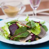 Fresh salad with lettuce leaves, boiled beef, beet, mustard Royalty Free Stock Images