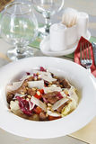 Fresh salad with meat and cedar nuts on a served table Royalty Free Stock Photo